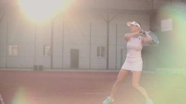 Tenisový hráč na hřišti útočí na létající míč, dynamický zápas tenisu na otevřeném dvoře.