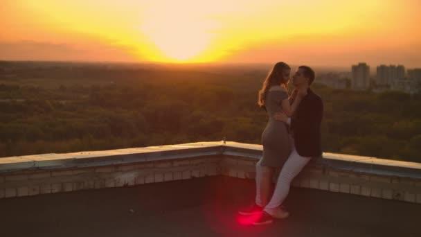Na střeše se nachází nádherný, sladký, krásný pár, s úžasným výhledem na západ slunce v městském městě. Navzájem se milují, že slunce velmi něžně přechází mezi vlasy.