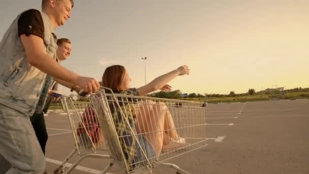 Young friends having fun on a shopping carts. Multiethnic young people playing with shopping cart.