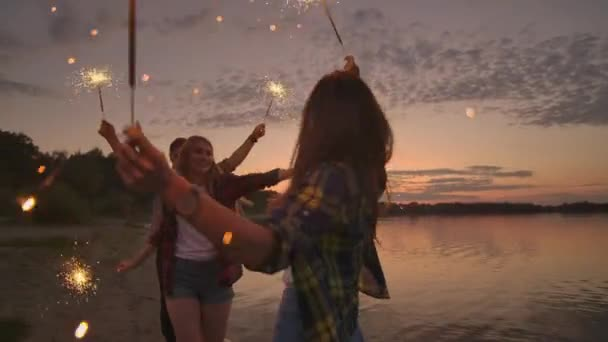 Cheerful male and female friends are running along the beach at sunset, holding sparkling fireworks and runaway lights in slow motion. Dancing and sunset party on the beach.