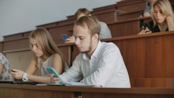 Multi etnická skupina studentů pomocí smartphone během přednášky. Mladí lidé pomocí sociálních médií a studium na univerzitě.