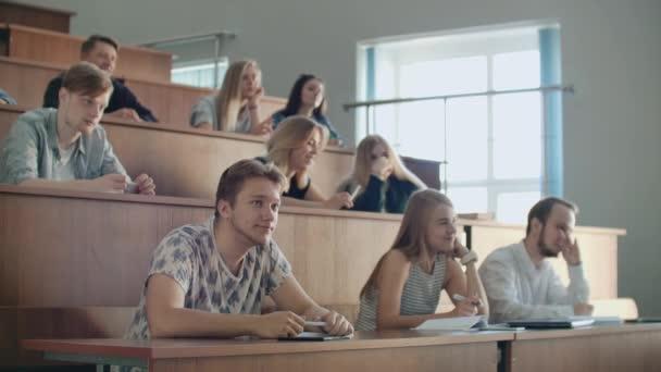 Egy csoport a hallgatók figyelmesen hallgat, és írja le a szavait a tanár a fórumon
