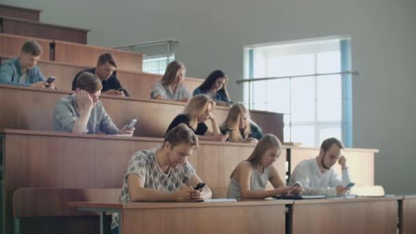 Egy unalmas előadás az egyetemen, a diákok Nézd meg a képernyők az okostelefonok. Sokan