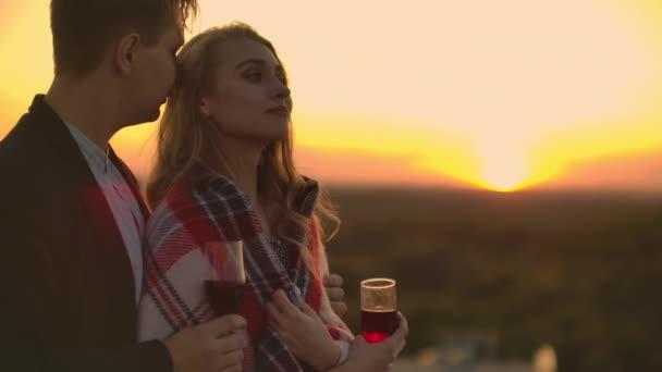 Szerelmesek felölelő srác lány nézi a naplementét bor áll a tetőn az épület. Egy házasságban élő fiatal házaspár kapcsolatának lassított képe