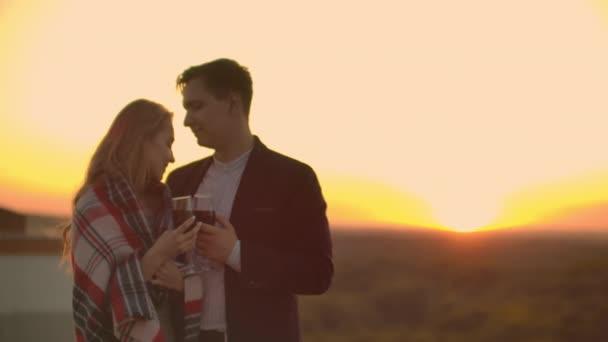 Fiatal házaspár a tetőn átölelve és ivott vörösbort a szemüveg álló öltözött kockás és csodáló a gyönyörű naplemente a város felett.
