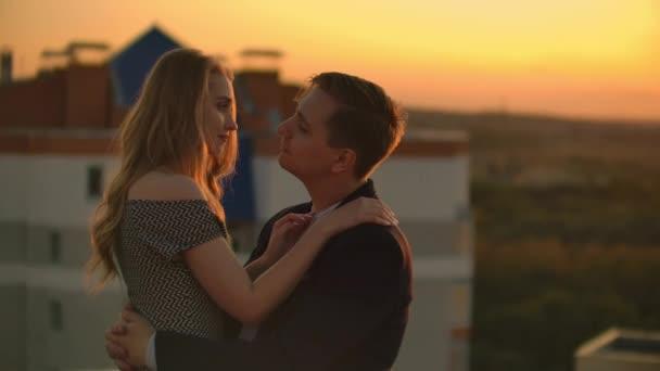 Egy férfi és egy nő ölelés a tetőn naplementekor
