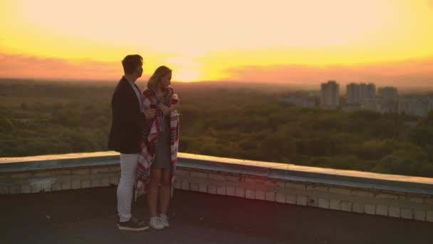 Liebhaber umarmen Kerl Mädchen beobachten den Sonnenuntergang mit Wein auf dem Dach des Gebäudes stehen. Zeitlupe über die Beziehung eines jungen Ehepaares