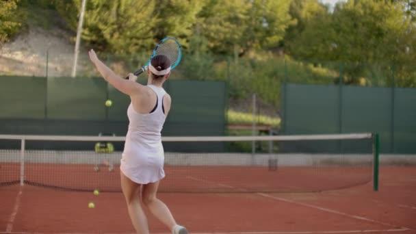 Ženská tenisová hráčka, co cvičila míč s trenérem, a v pomalém pohybu udeřil do míče. Profesionální výcvik tenisových hráčů