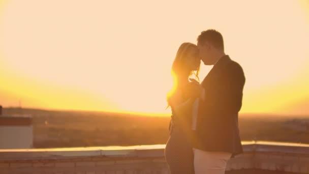 Zwei Liebende, ein Mann und eine Frau, lachen und tanzen bei Sonnenuntergang auf dem Dach. Glückliches Paar Sommer auf dem Dach in Zeitlupe