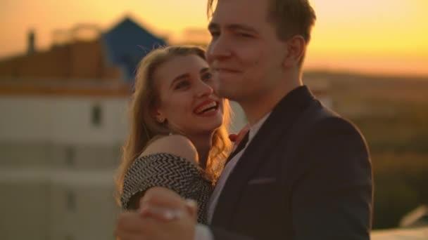 Dva milenci muž a žena se smějí a při západu slunce tančí na střeše. Zpomalit film šťastný pár léto na střeše