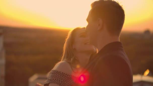 zwei Verliebte tanzen zusammen auf dem Dach bei Sonnenuntergang im Sonnenlicht