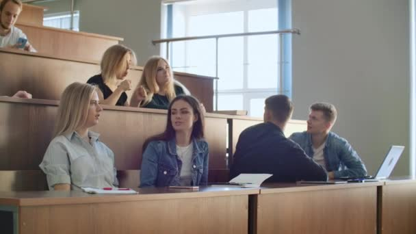 A large group of students during the break communicate with each other in the classroom. Modern College students communicate
