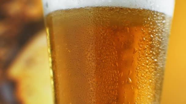 Studené světlé pivo ve sklenici s kapkami vody. Craft Beer zblízka. Otočení o 360 stupňů