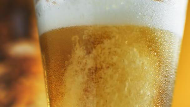 Makro snímek jemných bublin stoupající ve sklenici s pomerančovou kapalinou