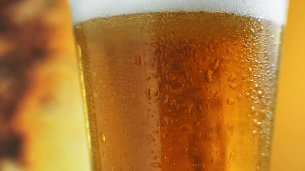 Sklenice piva zblízka s pěnou ve zpomaleném filmu