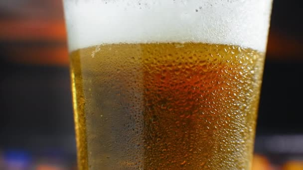 Zblízka zpomalený film: studené pivo ve sklenici velké kapky a bubliny v pivu.