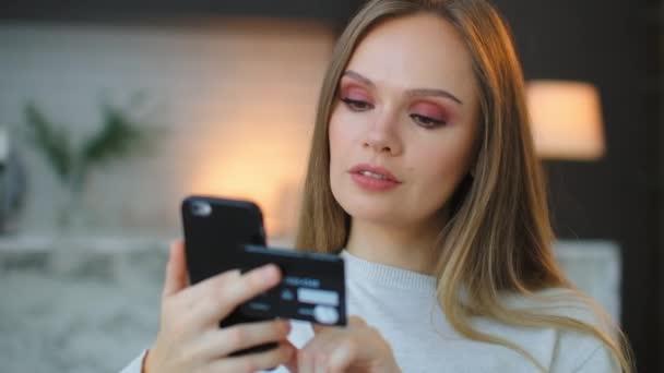 Eine Frau bestellt per Smartphone und Kreditkarte die Lieferung von Geschenken und Weihnachtseinkäufen. Banküberweisung mit Online-Banking