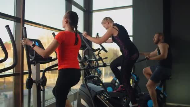 Junge, fitte Frau mit einem Ellipsentrainer in einem Fitnessstudio. Eine Gruppe junger Frauen trainiert an Sportgeräten in einem Fitnessstudio. Ständiger Nockenschuss.