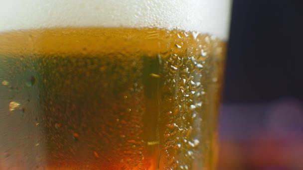 Makro záběr kapky přes sklenici piva. Pot na studené sklenici piva. Kapka kapky na sklenici plnou piva