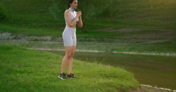 Lunges in the side. A woman does exercises for the muscles of her thighs and legs on the grass in a Park near the lake. Work with abs muscles. Slim, beautiful figure. Fitness marathon