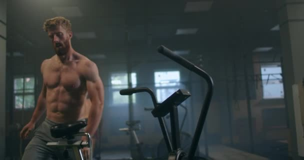 a man dominates an aerobics ride in the gym in slow motion. cardio training on a stationary bike