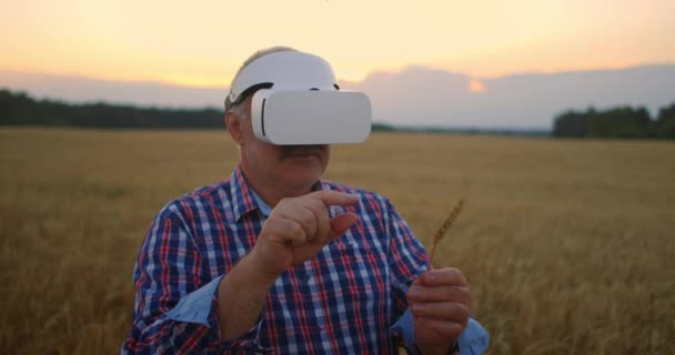 Älterer erwachsener Bauer in einem Virtual-Reality-Helm auf einem Getreidefeld. Im Sonnenuntergang bedient sich ein älterer Mann in einem Traktorfahrer einer Virtual-Reality-Brille. VR-Technologien und modernes Agrargeschäft