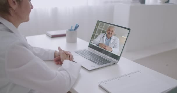 video conferencing of two physicians, man and woman are chatting by web camera of laptop in office of modern clinic