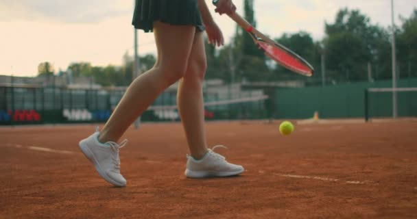 egy fiatal atléta lassított felvételű oldalnézete edzi a teniszlabda adogatását. Egy tinédzser atléta teniszezik a pályán. Egy aktív lány erőteljesen üti a labdát sportolás közben.