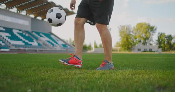 Professional Male soccer player athlete on the football field in slow motion in sports gear juggling a soccer ball