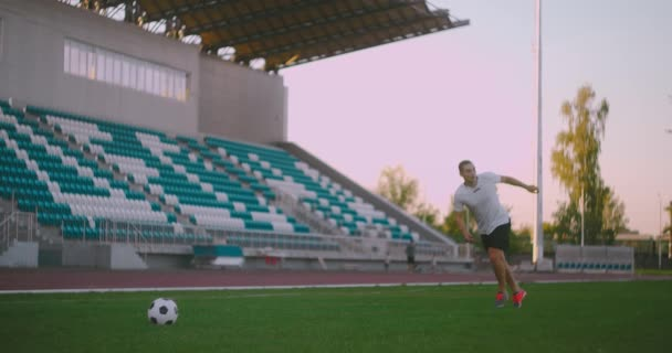 Set the socker ball on the lawn run and hit the ball in the stadium with a green lawn. A professional soccer player kicks the ball in slow motion