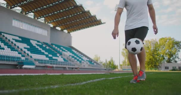 Professional Male soccer player athlete on the football field in slow motion in sports equipment juggles a soccer ball. A soccer player with a ball in the stadium near the keepy-uppies stands