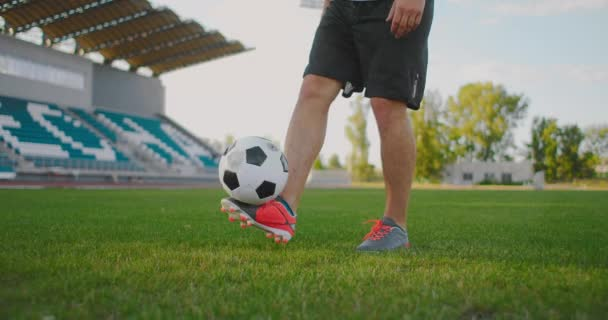 A male footballer juggles kicking a soccer ball in a slow-motion close-up. To stuff the ball.