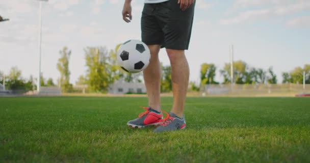 Professional Male soccer player athlete on the football field in slow motion in sports equipment bounce a soccer ball