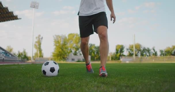 Detailní záběr mužského fotbalisty běžícího s fotbalovým míčem na fotbalovém hřišti na stadionu demonstrující vynikající driblování a ovládání míče.