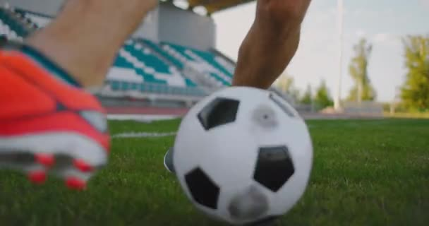 Close up of a male soccer player running with a soccer ball on the football field in the stadium demonstrating excellent dribbling