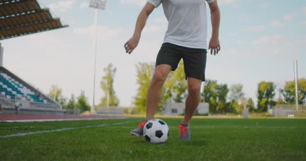 A soccer player at the stadium demonstrates dribbling with a soccer ball while leading a sword while running. Excellent skill of a football player and ball control
