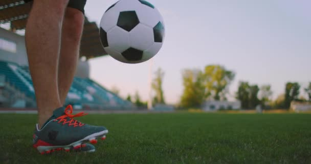 Tilt up with slow motion of male from professional soccer league juggling ball on leg in outdoor playing field on sunny summer day