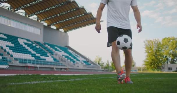 Profi férfi focista atléta a focipályán lassított felvételű sportfelszerelésben zsonglőrködik egy focilabdával. Egy focista egy labdával a stadionban a lelátó mellett.