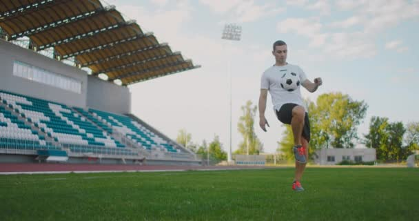 Professional Male soccer player athlete on the football field in slow motion in sports equipment juggles a soccer ball. A football player with a ball in the stadium near the stands