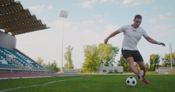 Ein Fußballer im Stadion demonstriert Dribbeln mit einem Fußball, während er beim Laufen ein Schwert führt. Hervorragende Fähigkeiten eines Fußballers und Ballkontrolle