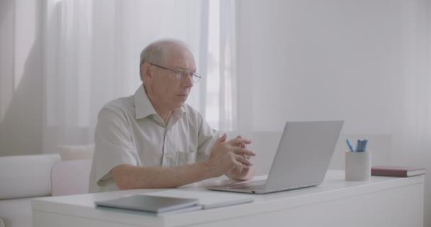 alter Mann führt Webinar mit Webkamera auf Notebook und Internet durch, sitzt zu Hause, Online-Kommunikation von Lehrern und Schülern