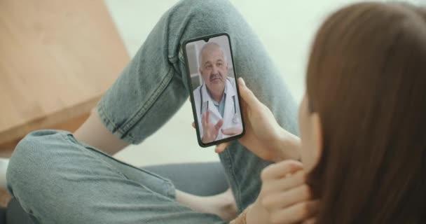 Arzthelferin trägt weißen Kittel, Kopfhörer-Video ruft entfernte Patientin auf dem Smartphone an. Arzt spricht mit Klient mittels virtueller Chat-Telefon-App. Telemedizin, Fernversorgung