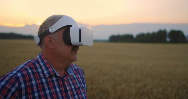 Starší farmář používá gesta s rukama na poli a brýlemi ve virtuální realitě. Používat VR brýle v zemědělství na poli s pšenicí.
