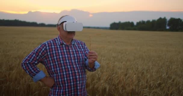 Starší farma používá VR helmu, když stojí na poli při západu slunce. Použít gesta pro virtuální realitu v zemědělství.