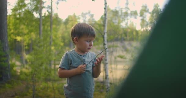 A fiú segít az apjának felállítani és felállítani egy sátrat az erdőben. Gyerekeket tanítani és együtt utazni egy sátortáborban.