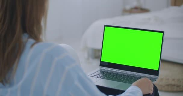Mladá žena doma pracuje na notebooku se zelenou maketou. Sedí na gauči v jeho útulném obýváku. Přes rameno Kamera Shot