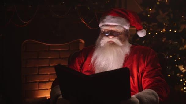 Mikulás ül a szobájában otthon közel karácsonyfa és pihenés a kandalló.