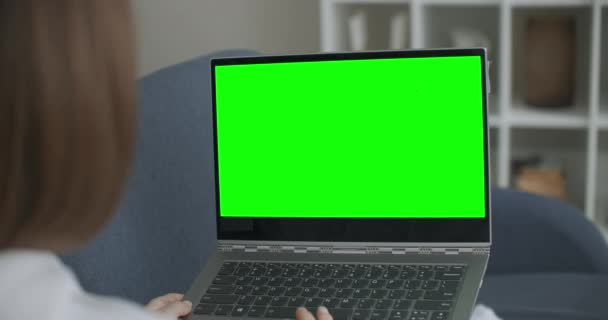 Žena doma sedí na gauči Pracuje na notebooku s Green Mock-up obrazovce. Coronavirus Covid-19 karanténní dálkové vzdělávání nebo pracovní koncept. Dívka používající počítač, prohlížení