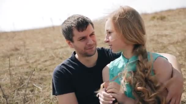 Fiatal pár. Egy férfi hugs egy nő, és a fülébe súgja. Piros zsinór.