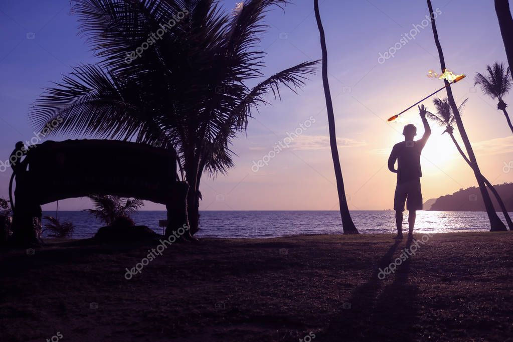 Man spinning contact staff or stick on the beach with sunrise background in the morning.